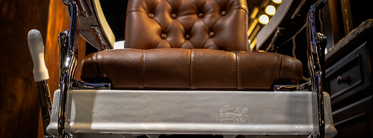 Image of a large brown leather barber chair.